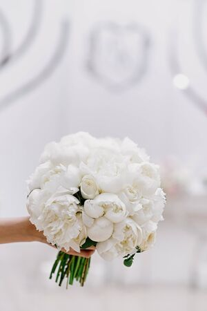 A gentle bouquet for a stylish bride of buds of white pioneers. Girl holds wedding bouquet