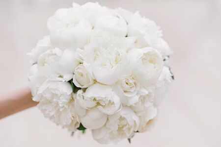A round and very beautiful bouquet of fresh buds of white pioneers for the bride. Bride s wedding accessory 스톡 콘텐츠