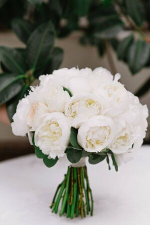 A stylish bouquet for brides made of buds of white round-shaped pioneers. Wedding bouquet of fresh flowers
