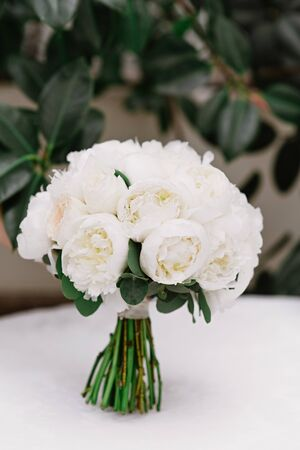 A beautiful bouquet for brides made of white round-shaped pines with natural stems. Modern wedding floristics