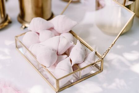 A beautiful air marshmallow in a glass box on a holiday table with sweets. Fresh, delicious sweets in beautiful dishes