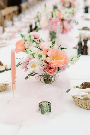A small elegant bouquet of an assortment of fresh flowers adorns the dining table at the wedding. Stylish wedding decoration with flowers and candles