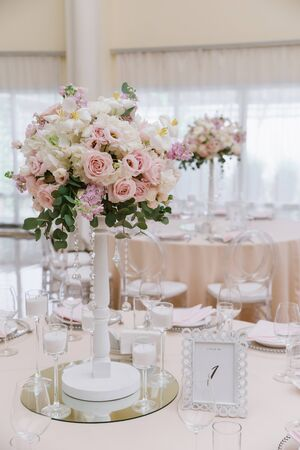Stylish wedding decor for a classic wedding in pastel shades. Beautiful wedding bouquet on a tall white stand adorns the festive table