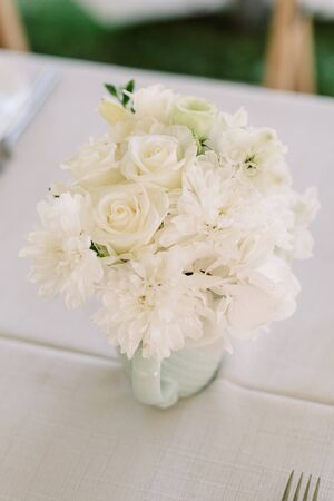 White rose buds and chrysanthemums decorate the dining table. Bouquet of fresh flowers. Wedding classical decor 스톡 콘텐츠