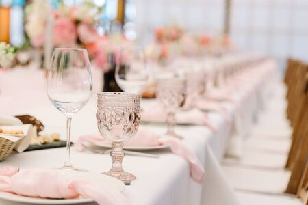 A luxurious crystal glass of pink glass with patterns stands on a banquet table. Stylish and expensive dishes on the holiday table