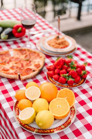 Table with bright, fresh fruit and other food outdoors for a seed lunch. Bright oranges and sweet strawberry 스톡 콘텐츠