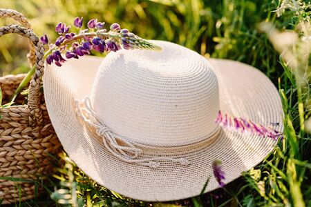 A large round female hat made of natural materials in rustic style. The hat lies on the grass. Beautiful summer wallpaper