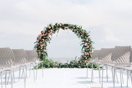 The round wedding arch is decorated with a variety of fresh flowers and greens.
