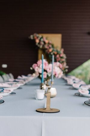 Beautiful artistic wedding design in soft colors with fresh pink flowers and thin candles. Table number