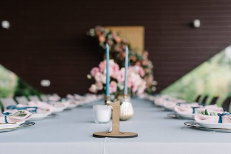 Table number, figure of wooden material. Thin candles in the candlesticks on the festive wedding table