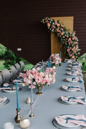 Long rectangular wedding table decorated with blue tablecloth, candles, luxurious flowers