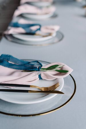 Luxury wedding table service with blue tablecloth and gentle pink napkins