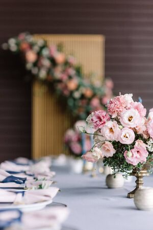 Luxurious wedding table for guests at the wedding. Pink flowers in beautiful vases