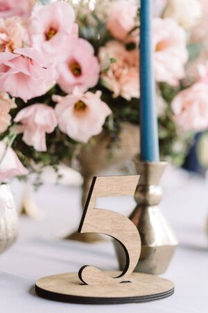 Elegant decor of a modern European wedding in a restaurant. A large bouquet of pink flowers and a stylish elegant wood table room. 스톡 콘텐츠