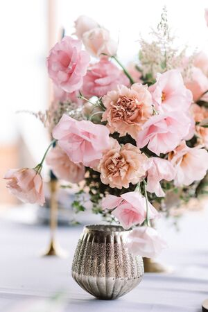 Decoration of the wedding with fresh flowers in pink color and in antique style. Wedding floristics against the bright background of the window