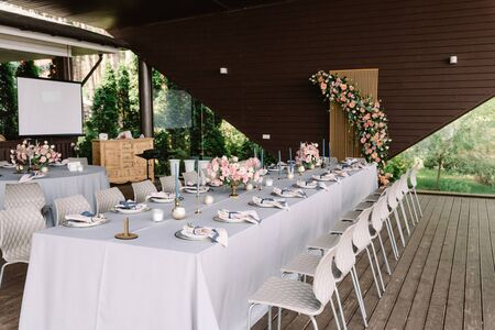 Beautiful service, pink flowers and candles on the table for a solemn reception. Long rectangular wedding table decorated with white tablecloth