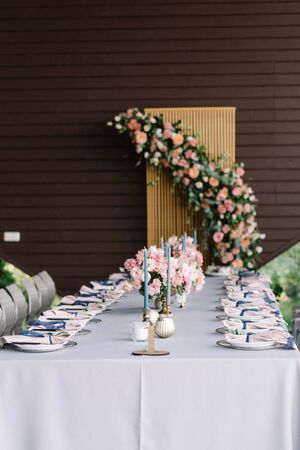 Long rectangular wedding table decorated with blue tablecloth, candles, luxurious flowers. Beautiful service, pink flowers and candles on the table for a solemn reception