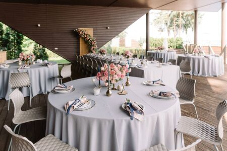Round banquet table in the restaurant. Modern wedding decor. Beautiful artistic wedding design in soft colors with fresh pink flowers and blue candles 스톡 콘텐츠