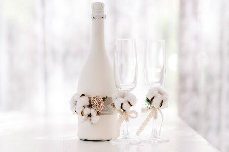 Duża butelka szampana ślubnego ozdobiona koronką wykonaną z worka i naturalnej bawełny. Okulary ślubne. Stylowe dodatki ślubne są białe w stylu rustykalnym