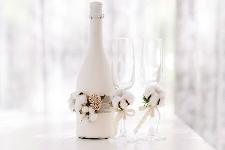 Une grande bouteille de champagne de mariage décorée de dentelle en sac et coton naturel. Verres de mariage. Les accessoires de mariage élégants sont blancs dans un style rustique