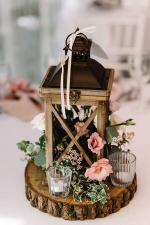 Wooden lantern filled with moss stands, white and pink flowers, small candlestick. Wedding decor made of natural materials in rustic style. Stockfoto