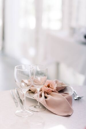 Empty glasses of clear glass near festive plate with pink cloth napkin. Wedding table service for reception of guests 스톡 콘텐츠
