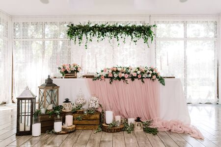Beautiful groom and bride table near large light windows decorated with natural materials. Lights, wooden parts and white candles stand on a parquet near the groom and bride s desk