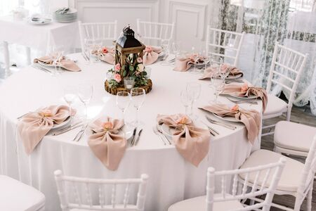 A beautiful round table for guests at a great wedding. Decoration of the wedding with decor made of natural materials and in pink color