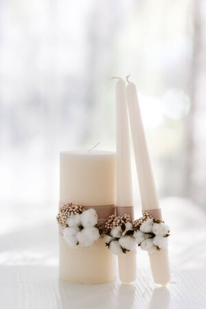 Elegant decoration of white wedding candles for the ceremony with white cotton and lace made of sackcover. Set of candles for family hearth