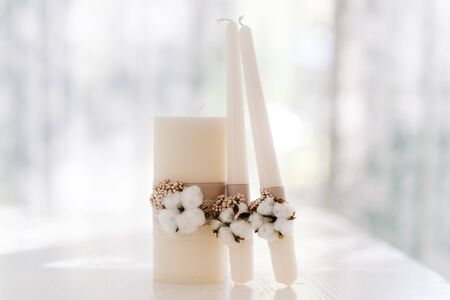 Stylish wedding accessories are white in rustic style. Set of candles for family hearth
