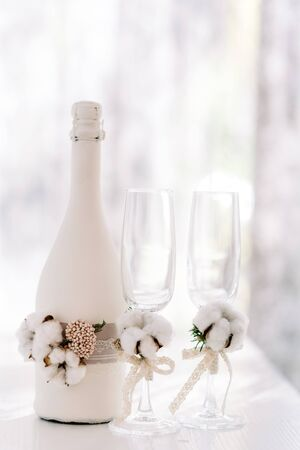 A large bottle of wedding champagne decorated lace made of sack and natural cotton. Stylish wedding glasses Stock Photo