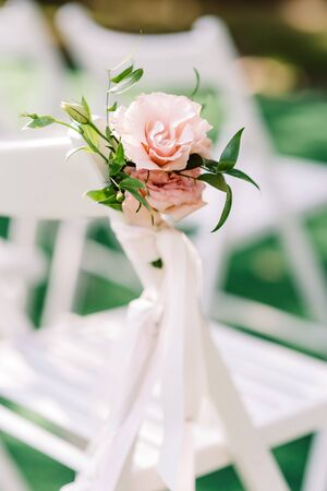 An elegant little bouquet of pink flowers and greens tied laterally on the back of a white chair. Wedding floristics for a modern wedding in the park