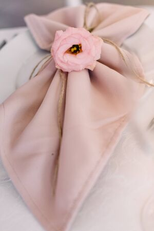 A little eustoma bud decorates a cloth napkin on a dinner plate. Wedding table service for reception of guests