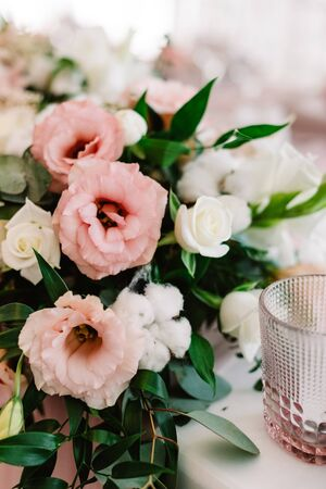 Art decoration of the dining table with small candles and fresh flowers. Pink and white eustoma on the wedding table 스톡 콘텐츠