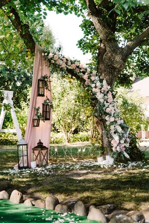 Natural decor for summer elegant wedding outdoors. Wedding ceremony near the tree. The luxurious design of the summer wedding in the garden 스톡 콘텐츠
