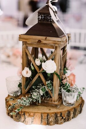 Wedding decor made of natural materials in rustic style. Wooden lantern filled with moss stands, white flowers and a small candlestick 스톡 콘텐츠