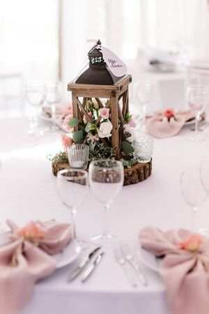 Beautiful wooden lantern filled with greens and flowers adorns a swollen table. The beautiful, original decor of wood, flowers and candles stands in the middle of the dining table