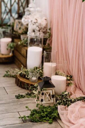 White bulk candles in glass containers stand near the groom and bride s beautiful table. Forest-style wedding decoration