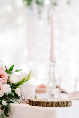 A tall thin paraffin candle of gentle pink color in a glass candlestick. Candles and natural plase of pine trees on the holiday table