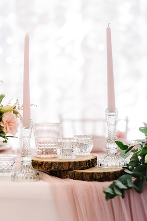 Candles and natural plase of pine trees on the holiday table. Thin tall candles in glass candlesticks