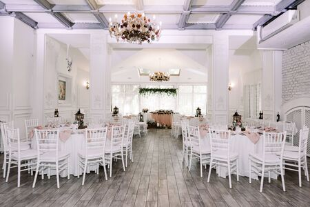 Beautiful banquet hall in the restaurant and elegant white tablecloths on tables. Round tables decorated with natural decor of wood and greens, candles and flowers. Foto de archivo