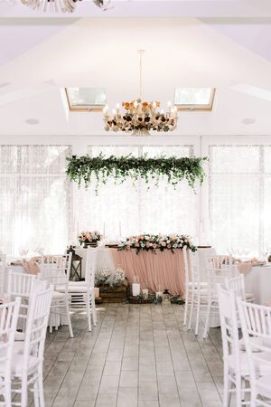 The groom and bride 's table in pastel shades, decorated with an assortment of fresh greens and flowers. Forest-style wedding presidium