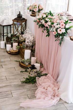 Beautiful flowers on the wedding table and candles in large glass flasks on wooden stands near it. Stylized wedding decor 스톡 콘텐츠
