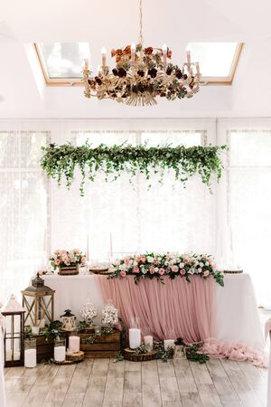 Lights, wooden parts and white candles stand on a parquet near the groom and bride desk. Beautiful groom and bride table near large light windows decorated with natural materials.
