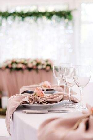 A beautiful table service at a modern wedding with burgeon of fresh flower on a beige napkin. Cutlery and glasses on the dining table Stock Photo