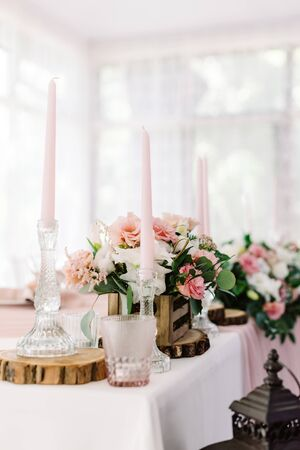Wedding decor in gentle shades and natural materials. Pale pink candles in tall glass candlesticks and flowers in a wooden little box