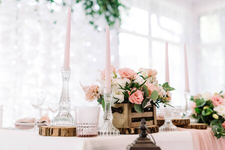 Pink candles in tall glass candlesticks and flowers in a wooden little box. Wedding decor in gentle shades and natural materials
