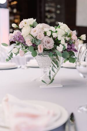 Beautiful flowers in a crystal vase decorate a festive table for guests of the groom and bride in the restaurant. Luxurious wedding floristics from living flowers