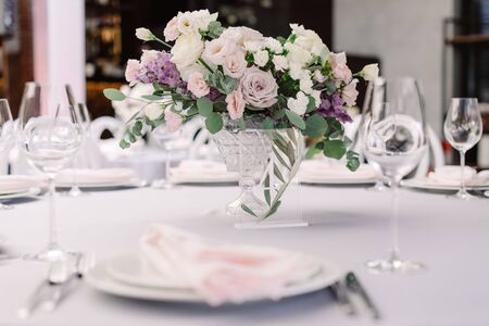 Luxurious fresh flowers in a glass vase decorate the wedding dining table. Beautiful bouquet on the holiday table