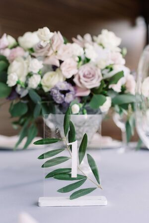 Holiday large table decorated with flowers for a solemn lunch at the wedding. Stylish decoration of modern wedding with fresh flowers and table number on a small glass stand.